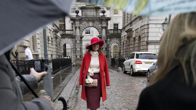 Carmen Negoita a fashion blogger poses for photographs between media umbrellas as rain falls on the first day of London Fashion Week, in London, Friday, Feb. 14, 2014. (AP Photo/Alastair Grant)