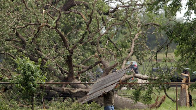 Eric Montez cleans up his place in Granbury, Texas, Friday, May 17, 2013. On Wednesday an EF-4 tornado hit the small north Texas town. (AP Photo/Mike Fuentes)