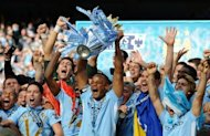 Manchester City&#39;s Belgian captain Vincent Kompany lifts the Premier league trophy after their 3-2 victory over Queens Park Rangers in Manchester on May 13, 2012. Manchester City won their first title since 1968