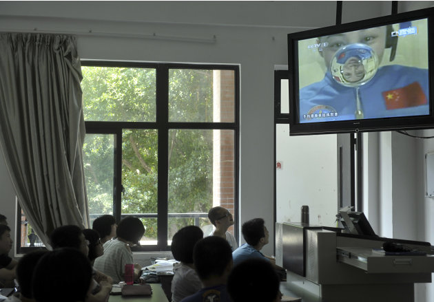 Students listen to a lecture delivered by Chinese female astronaut Wang Yaping broadcast live from onboard the Tiangong 1 prototype space station in a lab of a middle school in Fuzhou in southeast Chi