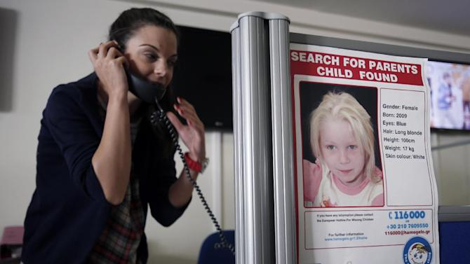 An employee of the ''Smile of the child'' speaks on the phone as a poster of the girl known as ''Maria'' is seen at the call center of the Greek charity in Athens, Monday, Oct. 21, 2013. The plight of an unknown girl found living with her alleged abductors in a Greek Roma settlement has triggered a global outpouring of sympathy and tips _ but no breakthrough in identifying the child, authorities said Monday. Greek investigators are considering everything from potential child trafficking to welfare scams or even simple charity as they seek the child's biological parents. (AP Photo/Thanassis Stavrakis)