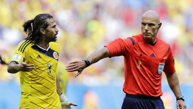 Referee Howard Webb, right, from England holds back Colombia's Mario Yepes during the group C World Cup soccer match between Colombia and Ivory Coast at the Estadio Nacional in Brasilia, Brazil, Thursday, June 19, 2014