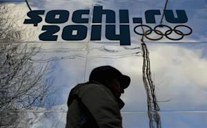 A man walks past a shop with an Olympic logo in the Black Sea resort town of Sochi