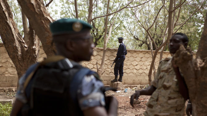 Soldiers stand guard to secure the perimeter while coup leader Capt. Amadou Haya Sanogo, not pictured, addresses journalists at junta headquarters in Kati, outside Bamako, Mali Friday, March 30, 2012. The junior officer who grabbed power in a coup says he plans to hold free elections and to rapidly return Mali to its established order, but refused to give a timetable even as neighboring countries prepare to enact severe financial sanctions.(AP Photo/Rebecca Blackwell)