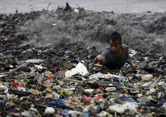 A boy is hit by waves at the height of Typhoon Nanmadol as he collects recyclable materials from garbage washed onto the shore along Manila Bay in Manila
