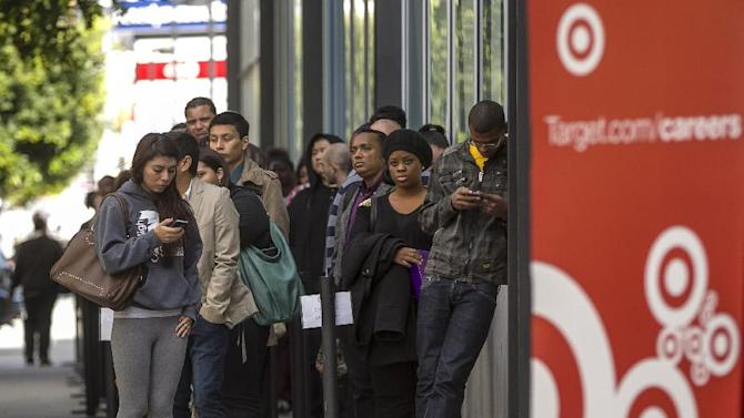 FILE - In this Thursday, Jan. 10, 2013, file photo, hundreds of prospective candidates await their turn to apply for job openings at a Target job fair in Los Angeles.T arget says its first-quarter adjusted profit will likely come in slightly below its forecast because of weaker-than-expected sales of seasonal and weather-sensitive items. (AP Photo/Damian Dovarganes, File)
