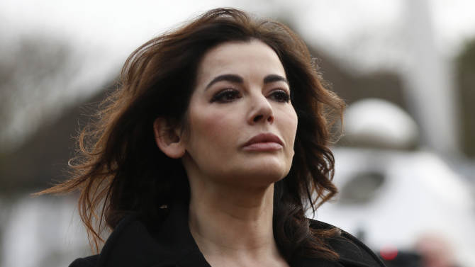 Celebrity chef, Nigella Lawson, arrives at Isleworth Crown Court in London, Thursday, Dec. 5, 2013. Lawson arrived at court on Thursday for a second day where she will testify as a prosecution witness at the trial of Elisabetta and Francesca Grillo, longtime employees who worked as nannies, cleaners and assistants in the couple's London home. The Grillos — sisters from Calabria in southern Italy — are accused of using credit cards loaned to them by Lawson and Saatchi for household expenses to spend 685,000 pounds (more than $1 million) on luxury clothes, accessories and rooms at high-end hotels. (AP Photo/Sang Tan)