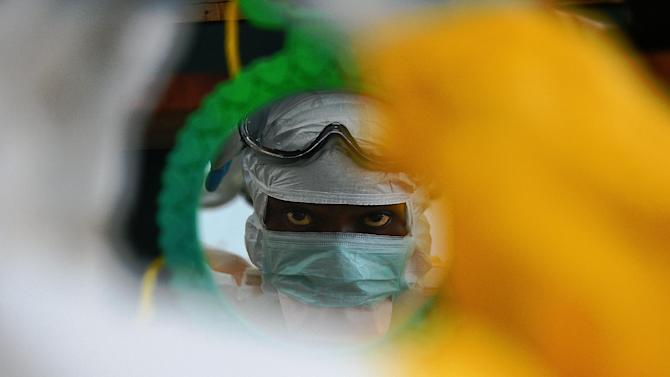 A medical worker checks their protective clothing in a mirror at a clinic in Kailahun, Sierra Leone on August 15, 2014