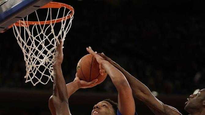 Duke's Jahlil Okafor, center, shoots past St. John's Chris Obekpa, left, and Sir'Dominic Pointer during the first half of an NCAA college basketball game Sunday, Jan. 25, 2015, in New York. (AP Photo/Seth Wenig)