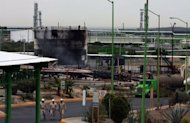 Workers of state-run Mexican energy giant PEMEX walk inside the gas plant, following a fire that caused the death of at least 26 people, in Reynosa, Tamaulipas state, on September 18, 2012
