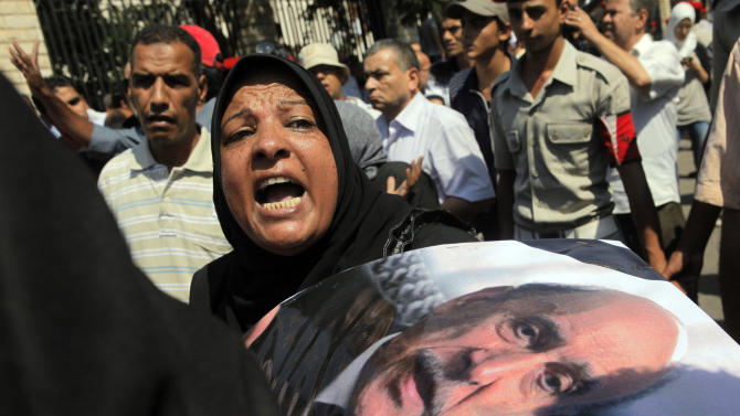 An Egyptian woman grieves during the military funeral honoring Egypt's former spy chief Omar Suleiman, seen in the poster at right, in Cairo, Egypt, Saturday, July 21, 2012. The 76-year-old Suleiman died Thursday in a U.S. hospital. The shadowy statesman was considered Mubarak's most trusted man, handing the regime's most sensitive issues like relations with the U.S. and Israel and the fierce battle against Islamists.  (AP Photo/Amr Nabil)