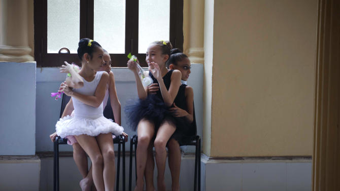 In this April 3, 2013 photo, young ballet students joke between them before their dance class at the National School of Ballet in Havana, Cuba. The school, housed in a graceful building that occupies a full half-block in colonial Old Havana, not only teaches dance, but subjects like language, math and history. (AP Photo/Ramon Espinosa)