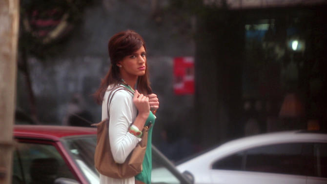 "In this undated image made from video released by the producers of ""Awel el Kheit"" or ""the Thread"" which airs on the private TV station ONTV, Waleed Hammad walks in a busy shopping district in Cairo, Egypt, dressed as a woman as a hidden camera crew films him for an investigative story on sexual harassment. The 24-year-old actor dressed conservatively for his mission into the secret world of sexual harassment and abuse on the streets of Cairo, donning a long skirt and sleeved shirt and covering his head like many Egyptian women.(AP Photo)"