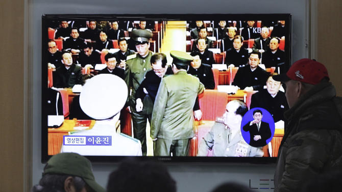 """People watch a TV news program at Seoul Railway Station, South Korea, Monday, Dec. 9, 2013 showing Jang Song Thaek, center, uncle of North Korean leader Kim Jong Un, being grabbed during an emergency meeting of Workers Party's Central Committee in Pyongyang the day before. North Korea announced Monday it had sacked leader Jang, long considered the country's No. 2 power, saying corruption, drug use, gambling, womanizing and generally leading a """"dissolute and depraved life"""" had caused Pyongyang's highest-profile fall from grace since Kim took power two years ago. (AP Photo/Ahn Young-joon)"""