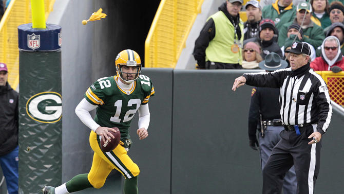 Green Bay Packers' Aaron Rodgers (12) scrambles as umpire Scott Dawson (70) throws a penalty flag during the first half of an NFL football game against the Tampa Bay Buccaneers Sunday, Nov. 20, 2011, in Green Bay, Wis. (AP Photo/Mike Roemer)