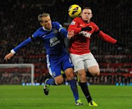Everton&#39;s English defender Phil Neville (L) tangles with Manchester United&#39;s English striker Wayne Rooney (R) during the English Premier League football match between Manchester United and Everton at Old Trafford, Manchester, North West England, on February 10, 2013. United won 2-0