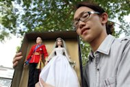A man displays dolls of Britain's Prince William (left) and his bride Catherine, the Duchess of Cambridge, outside the Hospis Malaysia in Kuala Lumpur on September 13. The royal couple will make a highly-anticipated public appearance Friday at a park in central Kuala Lumpur before visiting a nature conservation site in the Borneo jungle Saturday