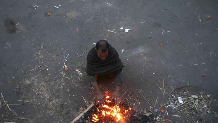 A man warms himself by a bonfire on a cold morning in Jammu