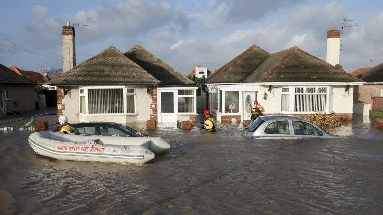 Emergency rescue service workers check houses in a flooded residential street in Rhyl