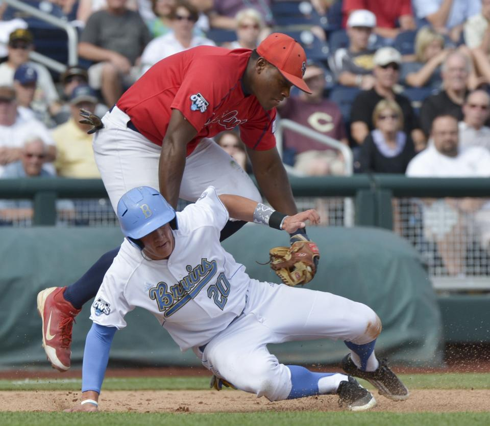 UCLA's Jeff Gelalich (20) is tagged out by Stony Brook third baseman William Carmona, in a rundown between second and third base on an attempted stolen base in the second inning of an NCAA College World Series baseball game in Omaha, Neb., Friday, June 15, 2012. (AP Photo/Ted Kirk)
