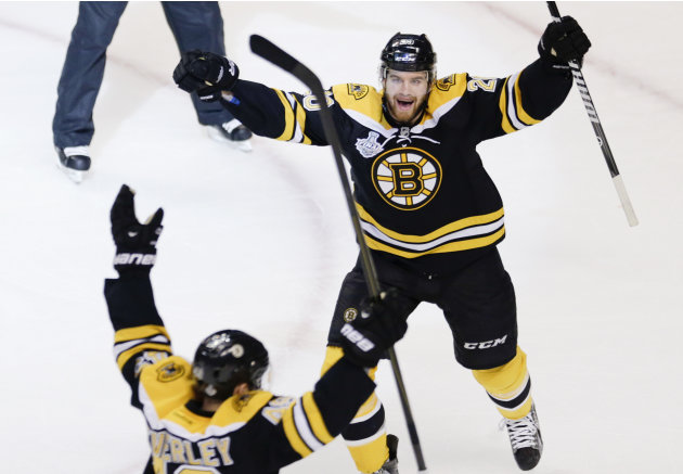 Boston Bruins left wing Daniel Paille, right, celebrates the goal by Bruins center Rich Peverley, front, against the Chicago Blackhawks during the first period in Game 4 of the NHL hockey Stanley Cup