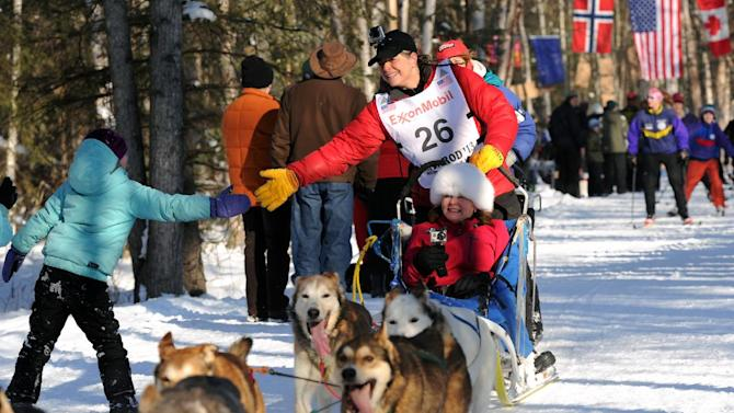 Jan Steves of Edmonds, Wash. greets a fan on the trail adjacent to Wesleyan Drive during the ceremonial start of the Iditarod Trail Sled Dog Race on Saturday, March 2, 2013, in Anchorage, Alaska. The competitive portion of the 1,000-mile race is scheduled to begin Sunday in Willow, Alaska. (AP Photo/Anchorage Daily News, Erik Hill)