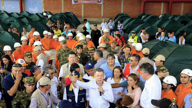 Colombia's President Juan Manuel Santos speaks to people deported from Venezuela during a visit at a temporary shelter in Villa del Rosario