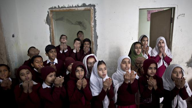 Pakistani schoolchildren chant prayers during a special class about the victims killed in Tuesday's Taliban attack on a military-run school in Peshawar, at Ranrra school in Rawalpindi, Pakistan, Friday, Dec. 19, 2014. Pakistani jets and ground forces killed 67 militants in a northwestern tribal region near the Afghan border, officials said Friday, days after Taliban fighters killed 148 people — most of them children — in a school massacre. (AP Photo/Muhammed Muheisen)