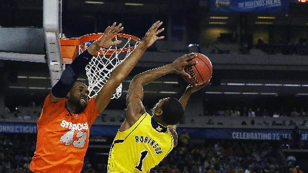 Michigan's Glenn Robinson III (1) shoots as Syracuse's James Southerland defends during the first half of an NCAA Final Four tournament college basketball semifinal game Saturday, April 6, 2013, in Atlanta. (AP Photo/David J. Phillip)