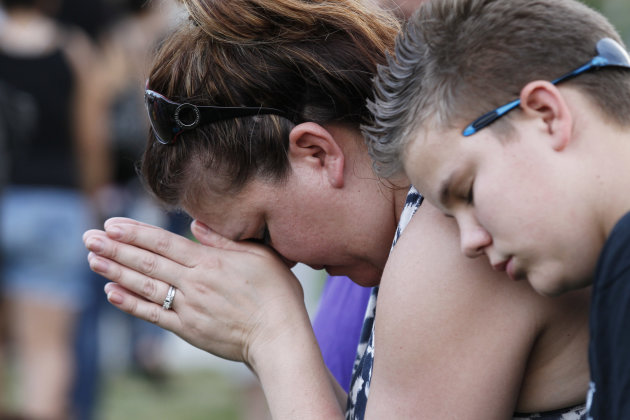 Dylan Bowen, 13, right, holds onto his mother Lorri Hastings, as they pray, Sunday, July 22, 2012 in Aurora, Colo., during a prayer vigil for the victims of Friday's mass shooting at a movie theater. 