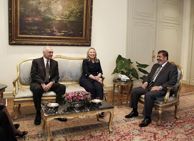 Egyptian Foreign Minister Mohammed Kamel Amr, left, U. S. Secretary of State Hillary Clinton, center, and Egyptian President Mohammed Morsi, laugh during a photo opportunity at their meeting at the Pr