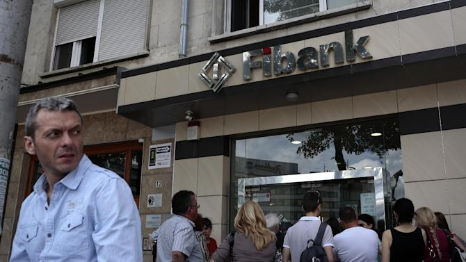 A man stands in front of the a branch of First Investment Bank as people still wait outside at the end of the working time, Sofia, Friday, June 27, 2014. A second Bulgarian bank has been hit by a run within the past week, prompting authorities to issue a statement claiming there is no reason for depositors to worry about their money despite reports the financial system is shaky. First Investment Bank, Bulgaria's third-largest lender, was the target of media rumors on Friday alleging that it was short on liquidity, causing public panic and a run on deposits. (AP Photo/Valentina Petrova)