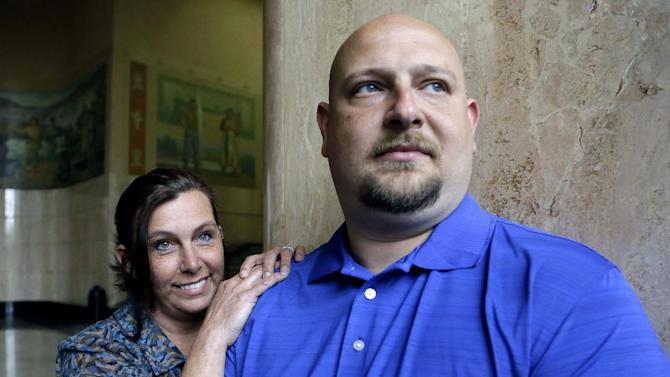 In this May 8, 2014 photo, former Spartanburg, S.C., sheriff's deputy Brandon Bentley, poses for a photo with his wife, retired Salem police department officer Kelly Clark, in Salem, Ore. Bentley's appeal to the South Carolina Supreme Court on a post-traumatic stress disorder claim was denied, stating the law did not provide mental health benefits for officers because they are trained in the use of deadly force and know that they may have to use it. (AP Photo/Don Ryan)