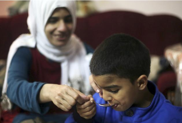 Sherien Fathy, a blind 32-year-old mother of two, feeds her son Yehia at her home in Cairo