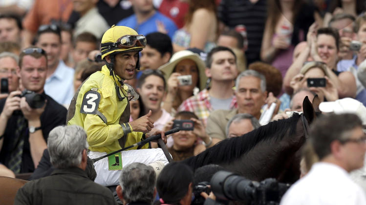 Jockey John Velazquez celebrates after riding Union Rags to victory in the Belmont Stakes horse race in Elmont, N.Y., Saturday, June 9, 2012. (AP Photo/David J. Phillip)