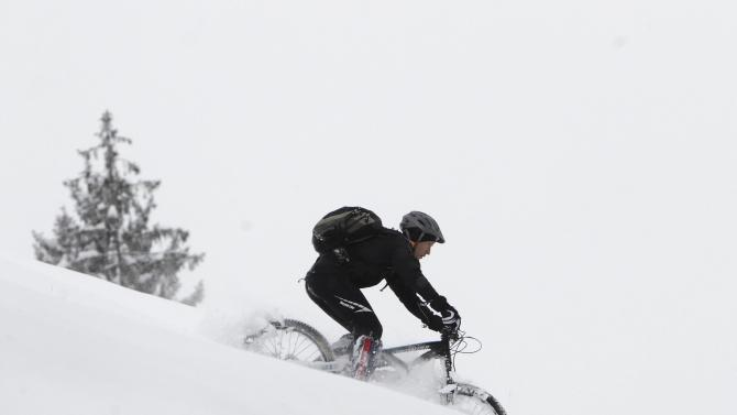 A man rides his bike through newly fallen snow in Medvode