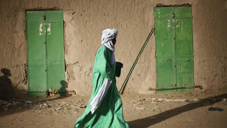 A Malian man dressed in green walks between green doors of closed shops in Gao, northern Mali, Tuesday Feb. 5, 2013.  Troops from France and Chad moved into Kidal in an effort to secure the strategic north Malian city, a French official said Tuesday, as the international force put further pressure on the Islamic extremists to push them out of their last major bastion of control in the north.(AP Photo/Jerome Delay)