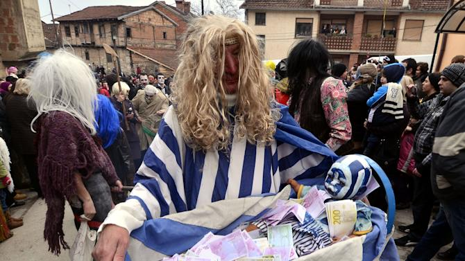 This picture taken Sunday, Jan. 13, 2013 shows a villager dressed up as a beggar with a baby, mocking Greece's crippled economy, during the carnival in Macedonia's southwestern village of Vevcani.  Said to date from pagan times 1,400 years ago, the Vevcani carnival, with its colorful floats and masked revelers, has grown in popularity over the last decade and attracts thousands of visitors for the celebrations on St. Vasilij Day to welcome in the New Year according to the Julian calendar. (AP Photo/Boris Grdanoski)