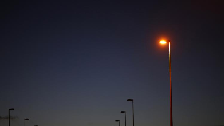 A lighted lamp post is pictured next to other lamp posts in a business park site where construction works have been halted, in Tomares