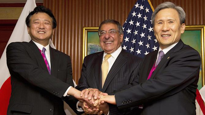 U.S. Defense Secretary Leon Panetta, center, shakes hands with Japanese Senior Vice Defense Minister Shu Watanabe, left, and South Korean Defense Minister Kim Kwan-Jin at a trilateral meeting during the International Institute for Strategic Studies (IISS) 11th Asia Security Summit in Singapore Saturday, June 2, 2012. (AP Photo/Jim Watson, Pool)