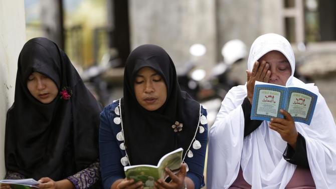 Acehnese women read religious verses as they pray at a mass graveyard for tsunami victims in Banda