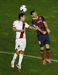 FC Barcelona's Lionel Messi from Argentina, right, in action with Rayo Vallecano's Raul Baena, left, during the Spanish La Liga soccer match at the Vallecas stadium in Madrid, Spain, Saturday, Sept. 21, 2013. (AP Photo/Andres Kudacki)