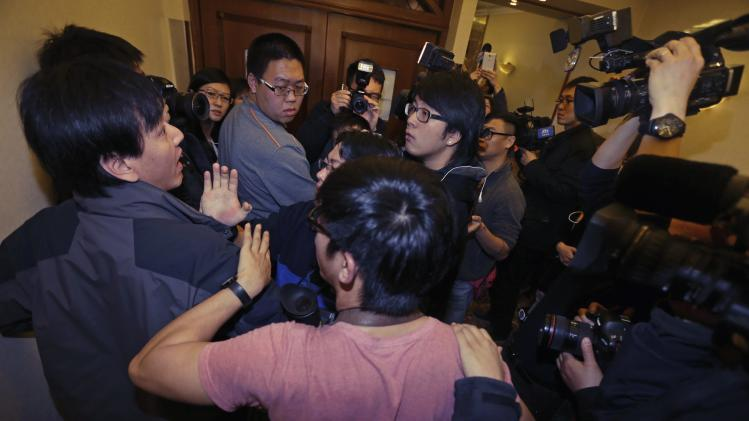 A journalist scuffles with another as they wait for relatives of passengers of Malaysia Airlines flight MH370 at a hotel in Beijing