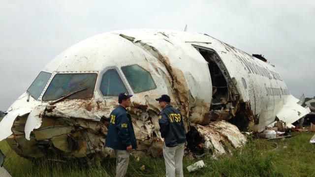 National Transportation Safety Board (NTSB) Investigators examine debris of a UPS A300 cargo plane after it crashed on approach at Birmingham-Shuttlesworth International Airport, Wednesday, Aug. 14, 2013, in Birmingham, Ala. The two pilots aboard the airplane were killed. (AP Photo/National Transportation Safety Board)