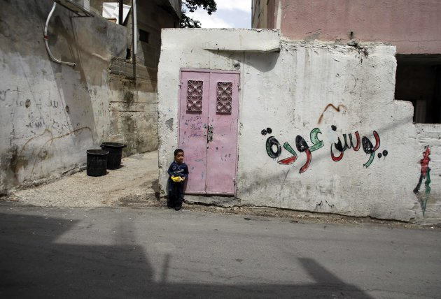 A Palestinian boy leans against the entrance to his house in Qalandiya Refugee Camp near Ramallah, ahead of Nakba Day