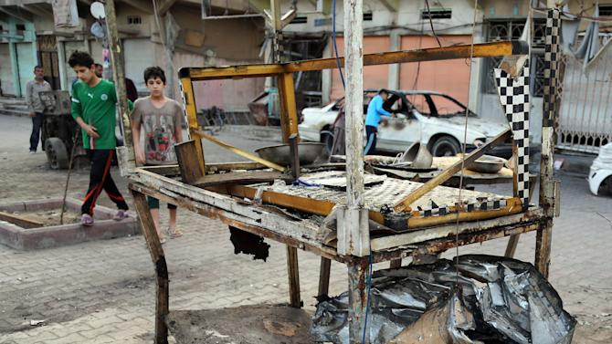 Civilians inspect damage in the aftermath of a Monday car bomb attack in a crowded commercial street in Baghdad's eastern neighborhood of Sadr City, Iraq, Tuesday, April 22, 2014. Suicide bombings and other attacks across Iraq killed and wounded dozens on Monday, officials said, the latest in an uptick in violence as the country counts down to crucial parliamentary elections later this month. (AP Photo/Karim Kadim)