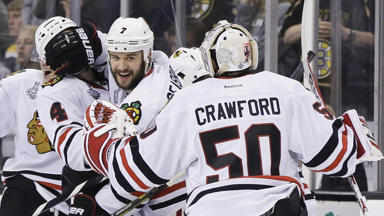 Chicago Blackhawks defenseman Brent Seabrook (7) celebrates his game-winning goal against the Boston Bruins with Chicago Blackhawks goalie Corey Crawford (50) during the first overtime period in Game 4 of the NHL hockey Stanley Cup Finals, Wednesday, June 19, 2013, in Boston. Chicago won 6-5. (AP Photo/Elise Amendola)