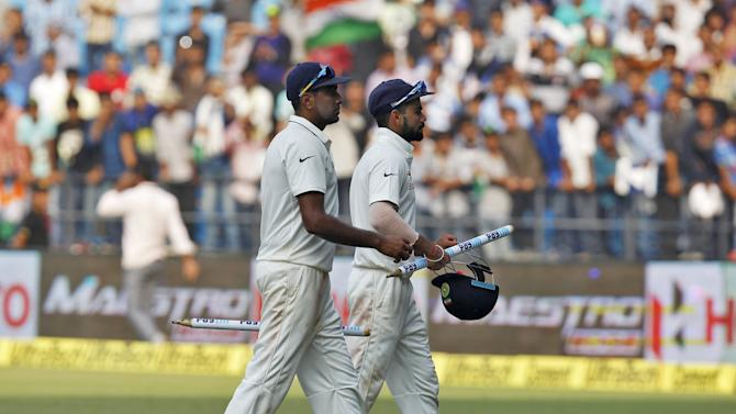 India's captain Kohli and his teammate Ashwin carry stumps as they walk towards the pavilion after their win over South Africa on the third day of their third test cricket match in Nagpur