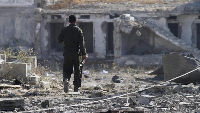 A member of the Hamas forces inspects damage to a Hamas security building following an Israeli air strike in Gaza City, early Saturday, June 23, 2012. A Gaza health official reported that at least one militant was killed and more than a dozen wounded during Israeli air strikes Saturday on the Gaza Strip. The Israeli military says the airstrikes target Palestinian militants who have fired over 150 rockets at residential areas in southern Israel this week (AP Photo/Hatem Moussa)