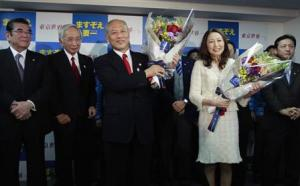 Japan's former Health Minister Masuzoe and his wife Masami hold flower bouquets while posing with his supporters at his office in Tokyo